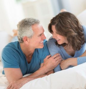 Model image showing a middle-aged man and woman lying in bed on stomach smiling at each other, depicting no sleep apnea, Charlotte, NC.
