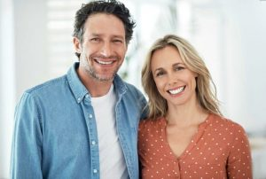 stock image of a man and woman smiling for blog about the benefits of professional teeth whitening in Charlotte