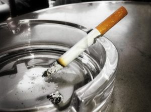 stock image of a cigarette on an ash tray for a blog about how smoking affects your teeth in Charlotte, NC